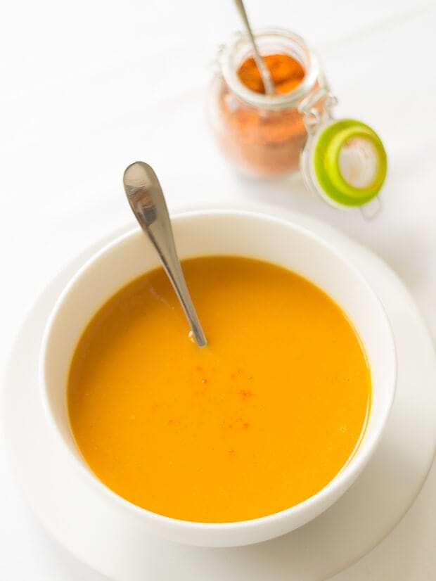 Birds eye view of a bowl of healthy carrot sweet potato soup with a soup spoon in and dish of chilli powder in the background.