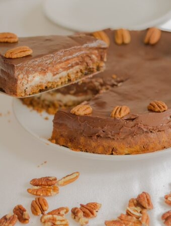 Chocolate ganache cheesecake with a slice being lifted out. Pecan nuts decorated around the cheesecake.