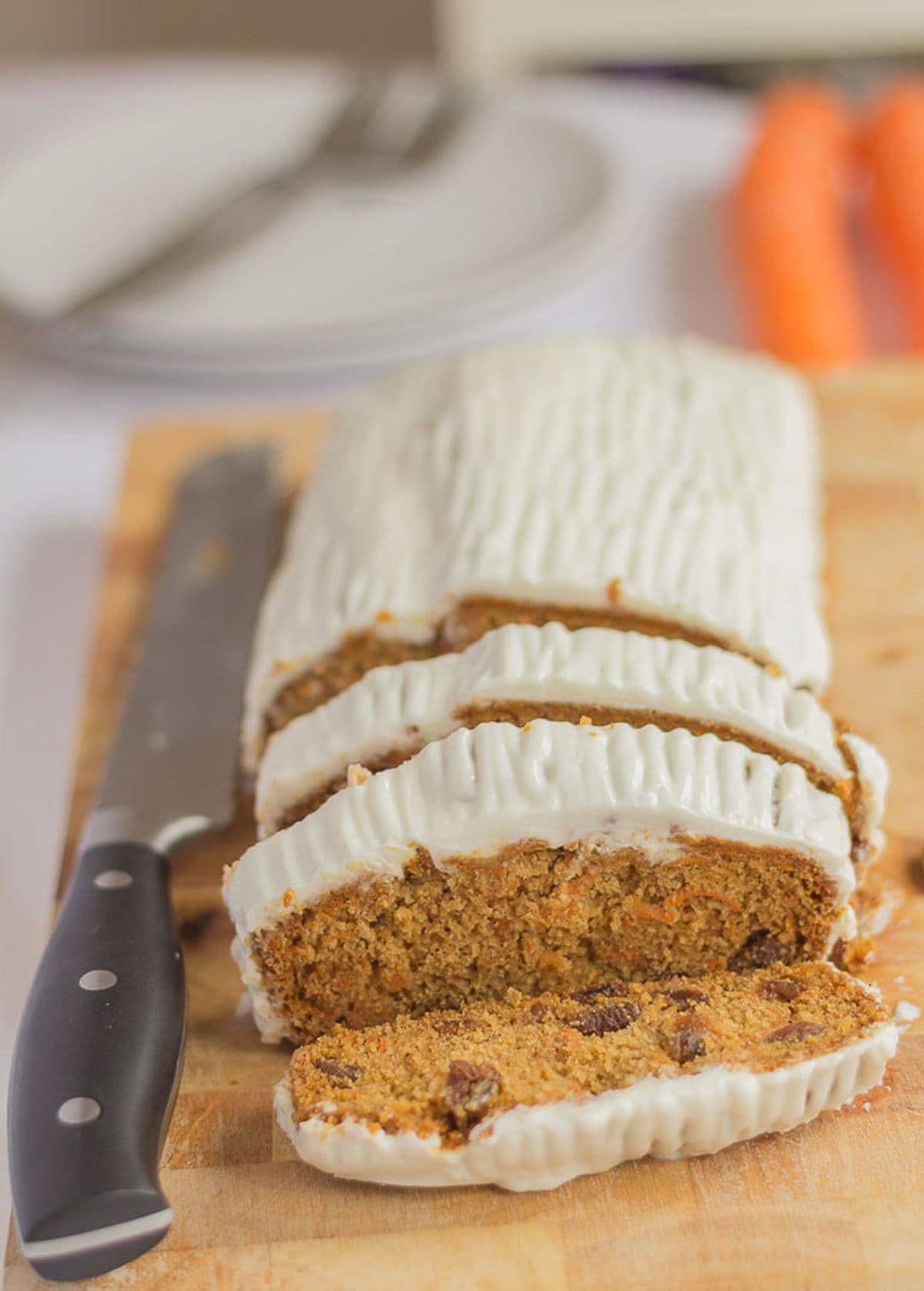 Gluten free carrot and sultata cake on a chopping board. Three slices cut off with a carving knife to the right.