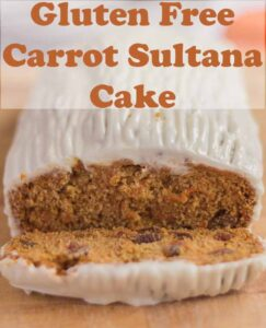 Gluten free carrot sultana cake on a bread board with a slice cut off the front. Pin title text overlay at top.
