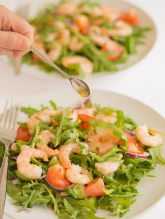 Two plates of king prawn and rocket salad one in front of the other. Dressing being added by teaspoon to the front plate.