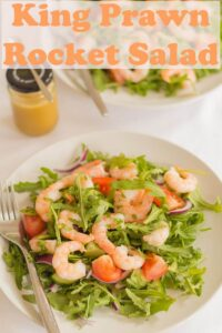 A plate of king prawn and rocket salad with dressing shaker in the background.