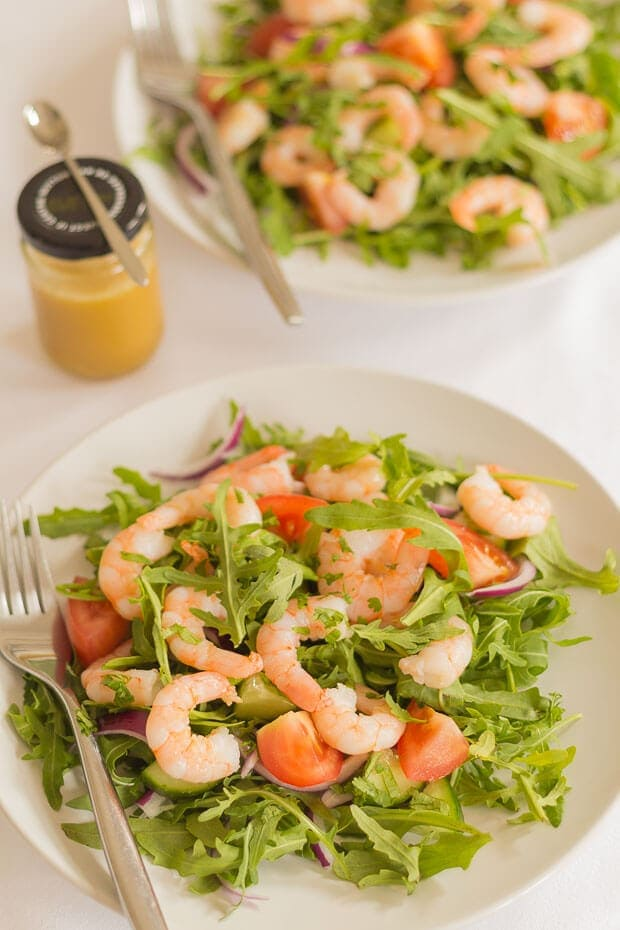 Two plates of king prawn and rocket salad with a jar of dressing in between.