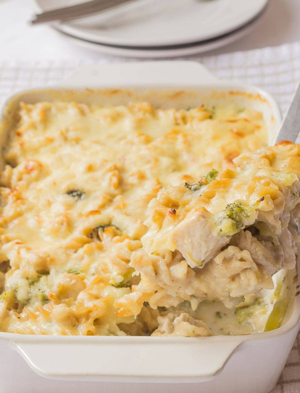 A slice of chicken broccoli stilton pasta bake being lifted from the cooked casserole dish.