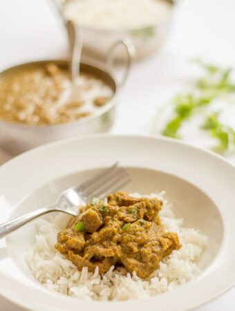 Mild beef curry served on a bed of rice. Balti dishes of beef curry and rice in the background.