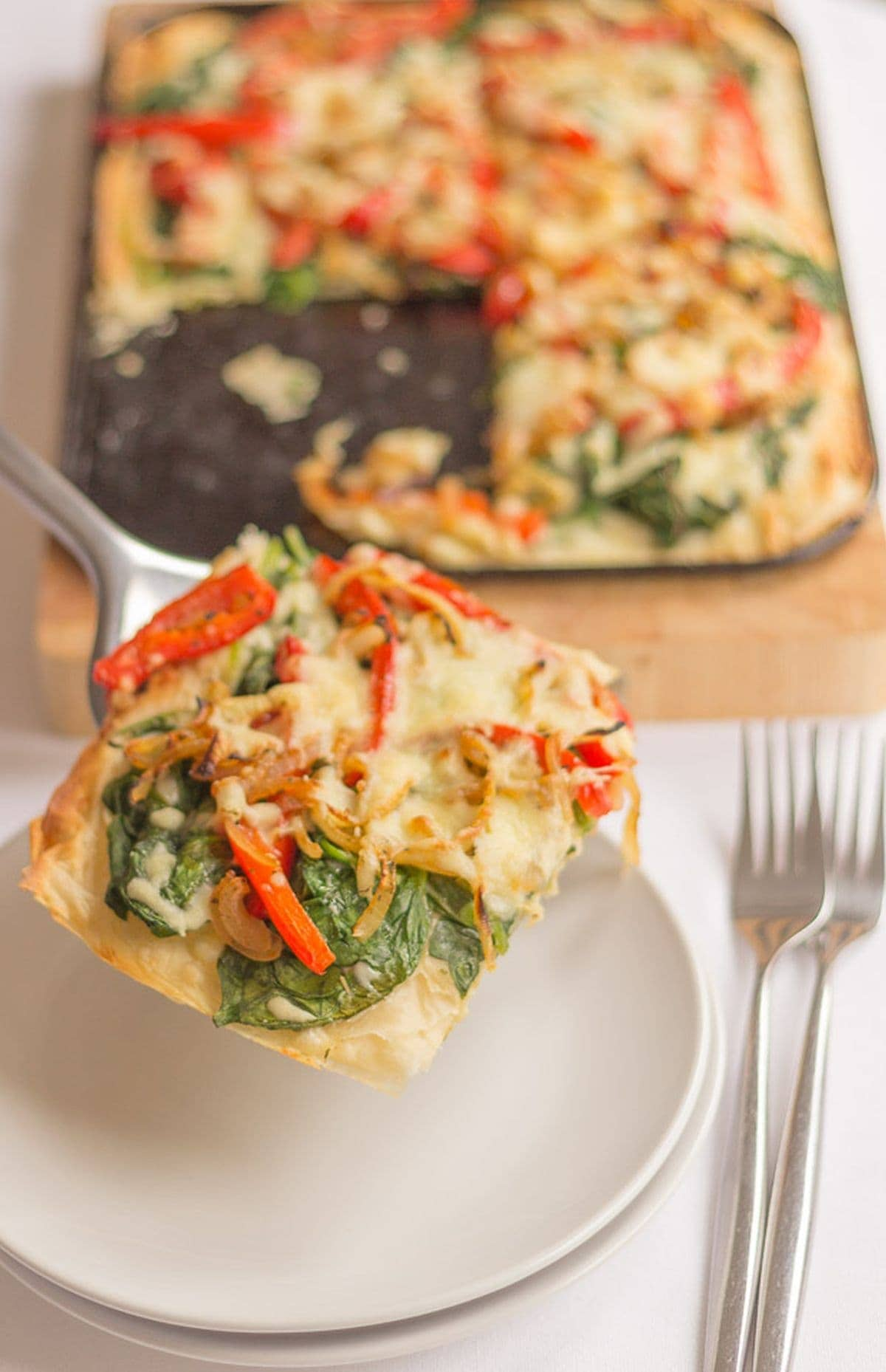 A slice of red pepper and spinach filo tart being lifted onto a plate by a slce from the red of the tart on the tray in the background.