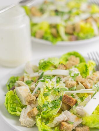 Two plates of chicken caesar salad one in front of the other with a jar of dressing in between.