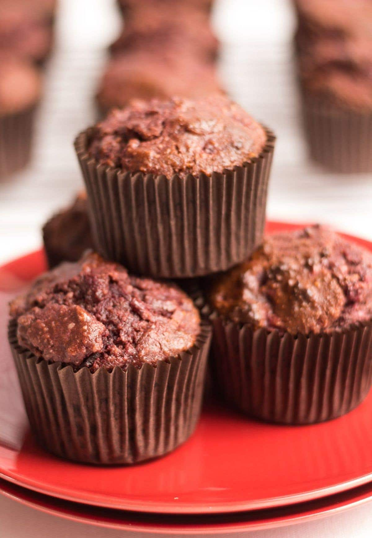 Three gluten free chocolate and beetroot muffins stacked on top of two plates.