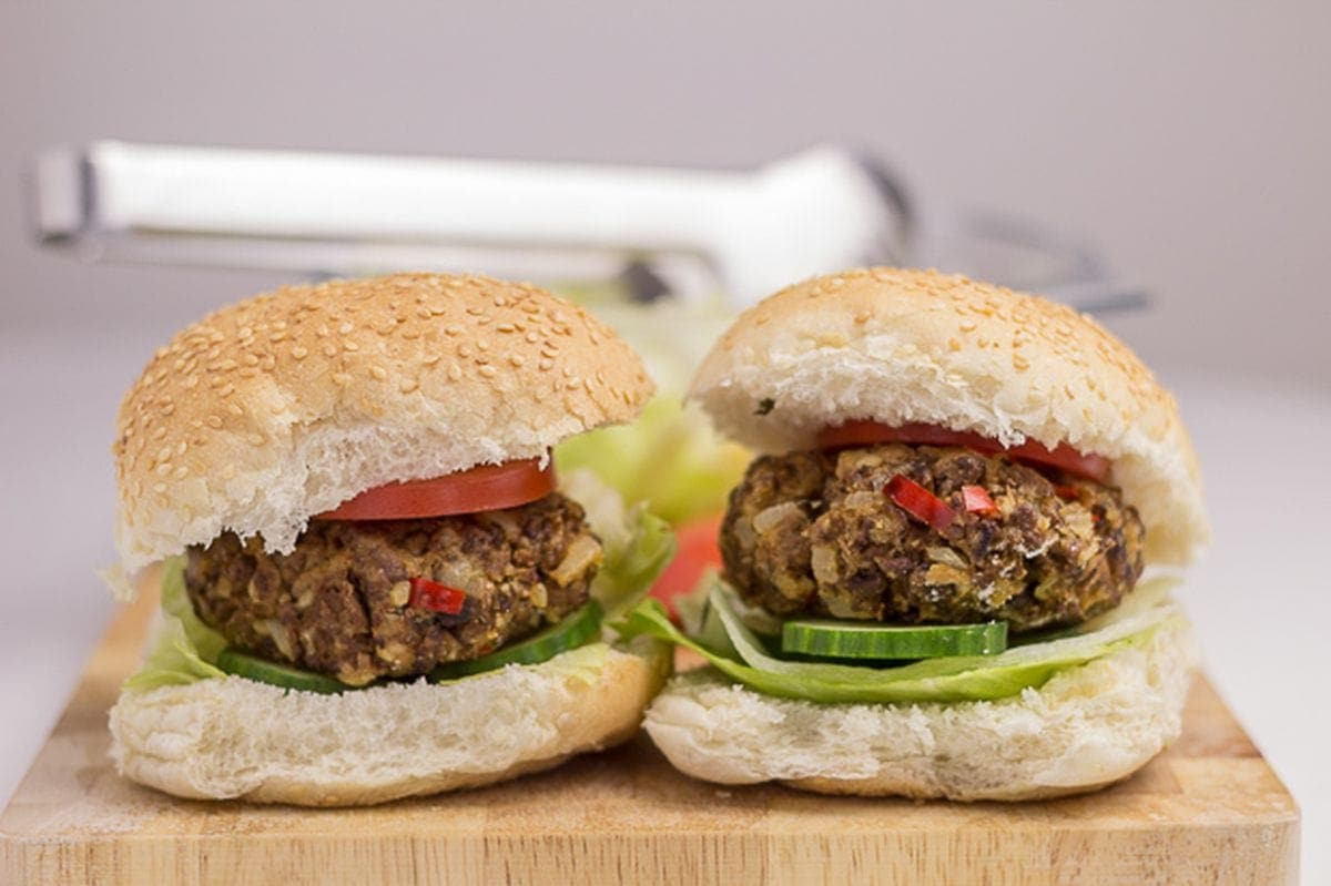 Two home-made quorn burgers in burger buns with lettuce and tomato garnish side by side on a chopping board.