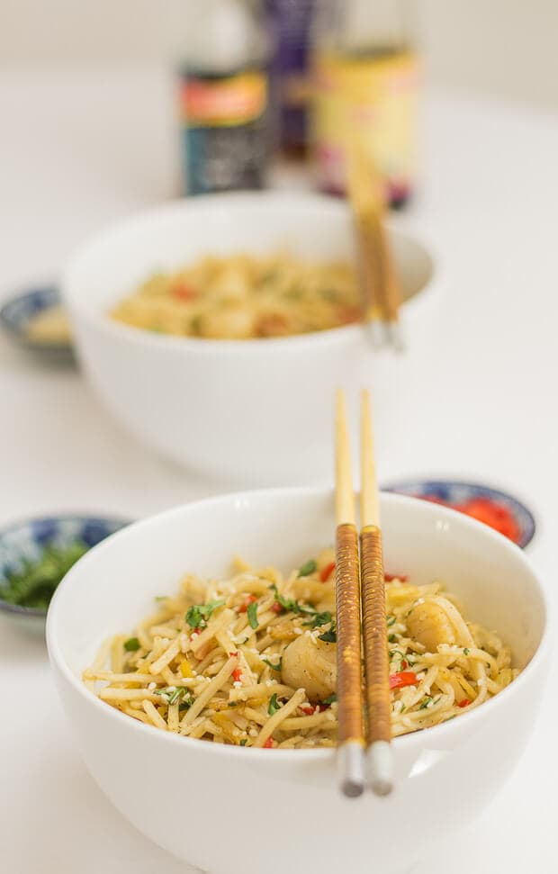 Two bowls of stir fried scallops with whole wheat noodles one in front of the other with chop sticks laid over the top of each bowl.