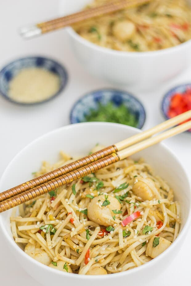 Birds eye view of a bowl of stir fried scallops with whole wheat noodles. Chop sticks laid across the top.