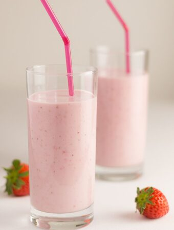 Two tall glasses of strawberries and cream smoothies one in front of the other with straws in.