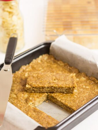 A square tin of no-bake almond oat bars. One bar removed and placed on top with a spatula to the side.