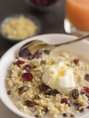 Bowl of overnight breakfast rice pudding topped with nuts and seeds and yogurt.
