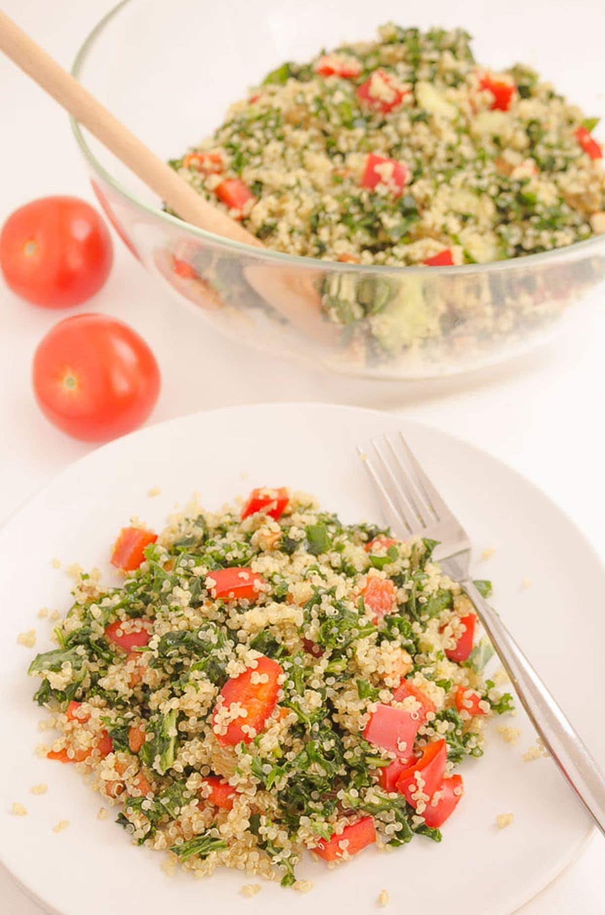 A plate of served quinoa kale almond salad with the rest of the salad in a bowl in the background.