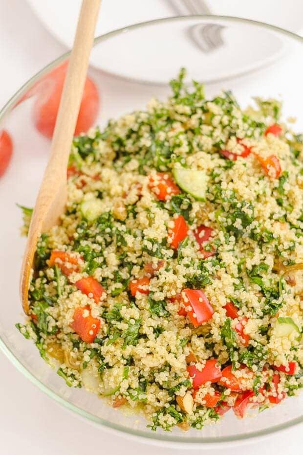 Birds eye view of a bowl of quinoa kale almond salad with a wooden spoon in.