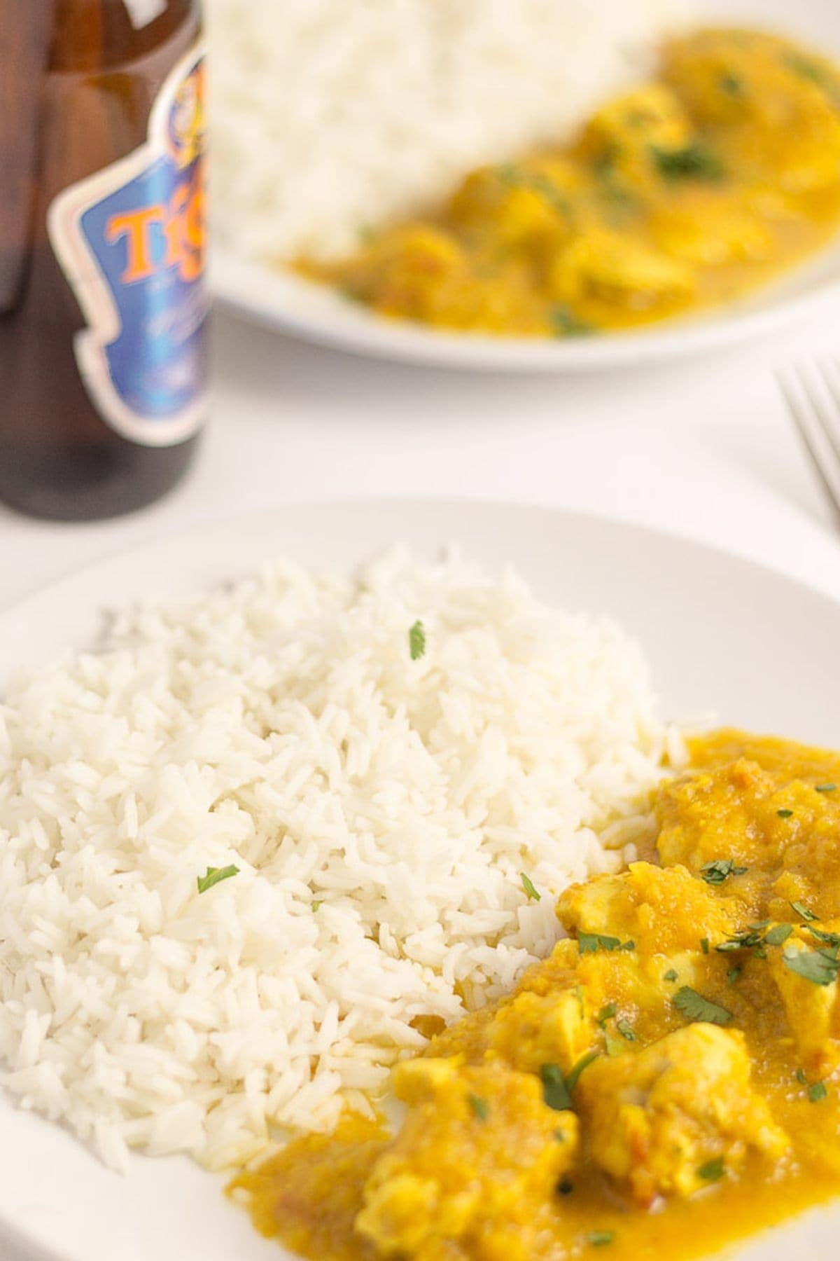 Two plates of chicken curry with rice on and a bottle of beer in between.