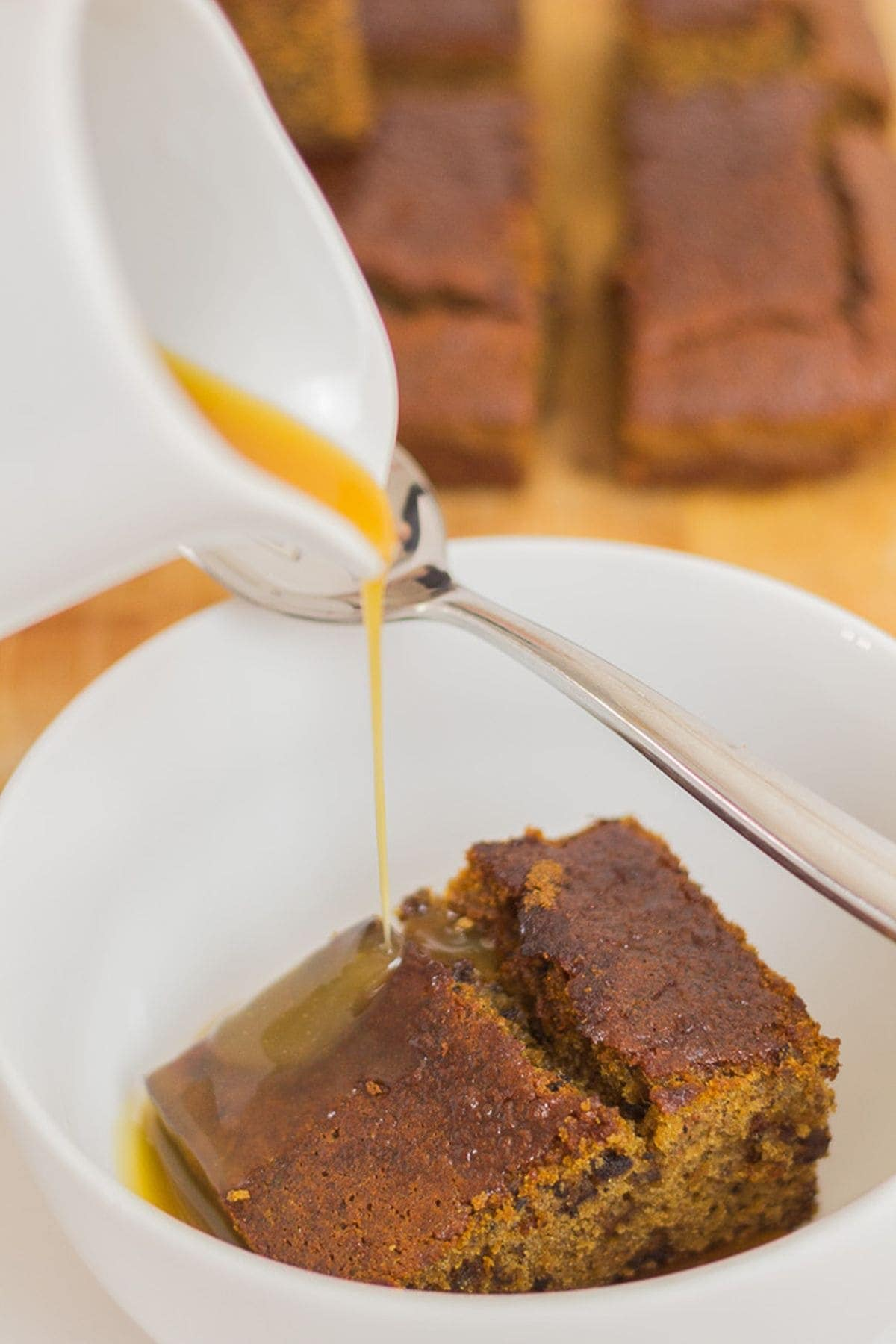 Gluten free sticky toffee pudding in a bowl with a jug pouring over the toffee sauce.