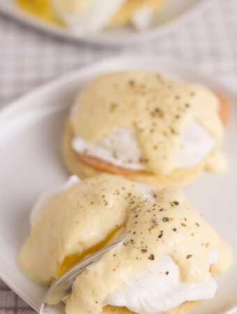 A square plate with two healthy eggs benedict servings. One with a fork breaking open the egg to show the runny yolk.
