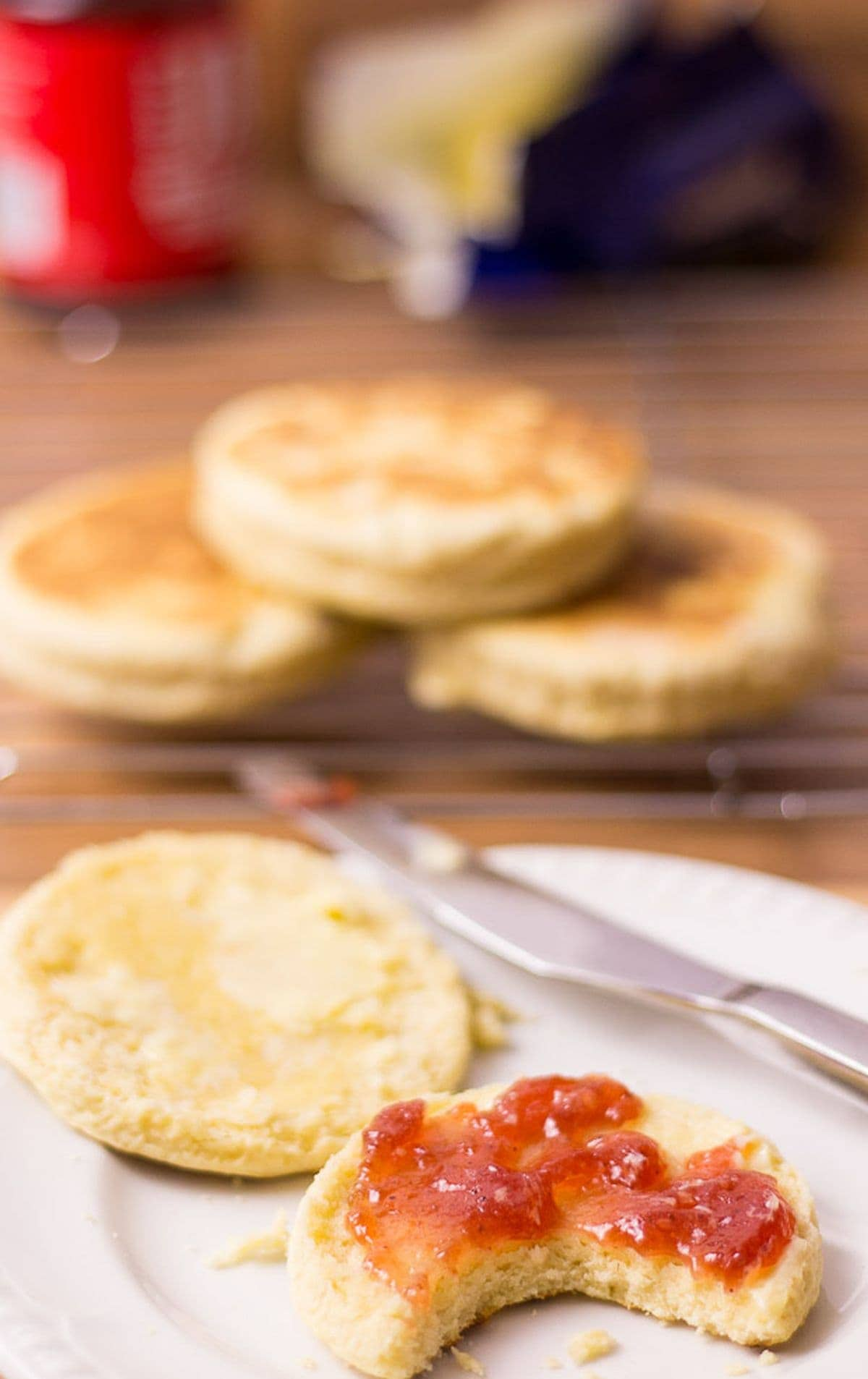 Two quick English muffins on a plate. One with jam on and a bite taken out. The rest of the muffins on a wire rack in the background.