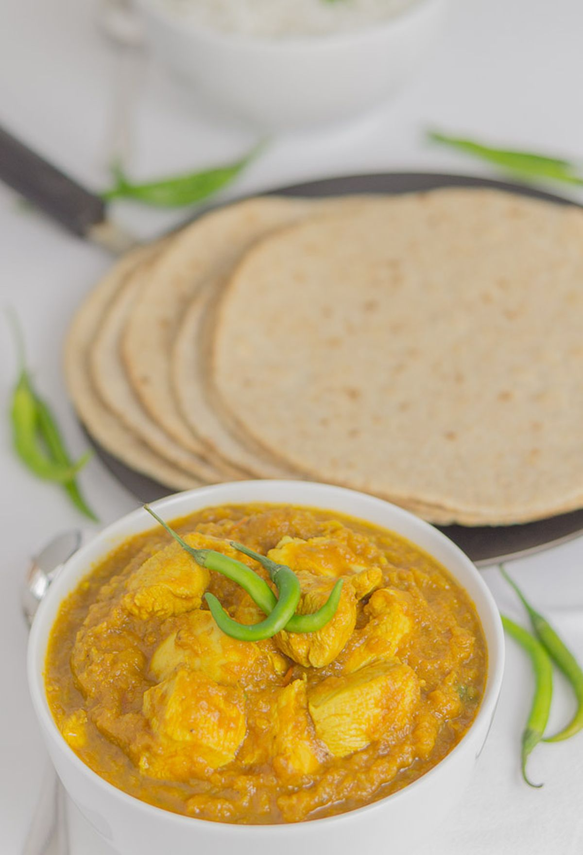 A bowl of green chilli chicken curry garnished with green chillies and some paratha breads on a tava in the background.