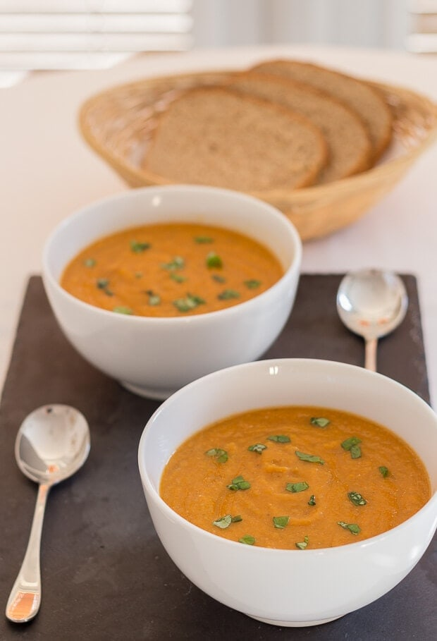 Two bowls of tomato and green lentil soup diagonally opposite each other on a black slate with spoons beside. A basked of sliced bread in the background.
