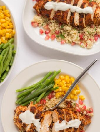 Birds eye view of a plate of Cajun spiced chicken with pomegranate couscous served with green beans and sweetorn.