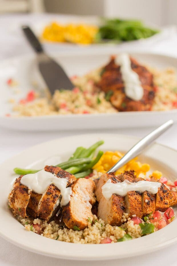 Cajun spiced chicken on a bed of pomegranate couscous served with green beans and sweetcorn. A serving dish with another portion of chicken in the background.