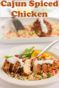A plate of Cajun spiced chicken served on pomegranate couscous. Pin title text overlay at top.