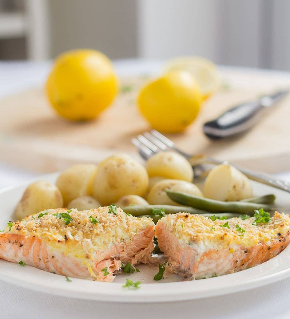 A plate with oven baked salmon with cream cheese served with baby potatoes and green beans. A chopping board with lemons on in the background.