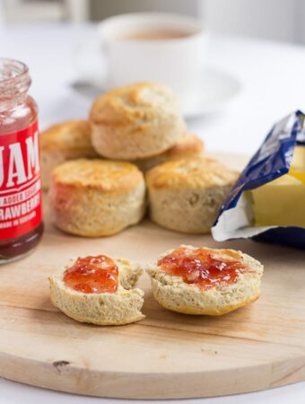 A Scottish bran scone cut in half and covered with butter and jam on a chopping board. More scones in the background as well as a jar of jam, block of butter and a cup of tea.