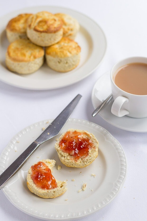 A plate with Scottish bran scones cut in half and covered with butter and jam and knife to the side. Another plate with 5 scones on at the top and a cup of tea to the right hand side.