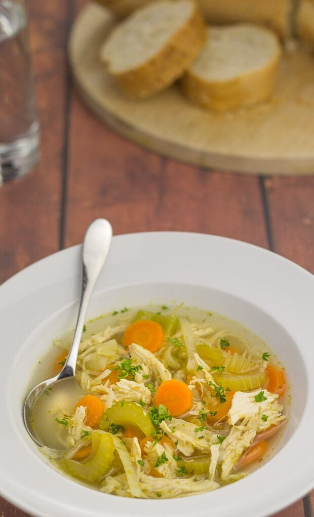 Close up of a bowl of simple chicken and vegetable soup with a spoon in.