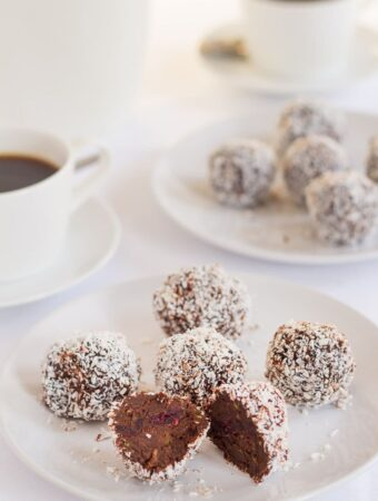 A plate of chocolate cranberry truffles with one cut in half. Another plate in the background as well as two cups of coffee.