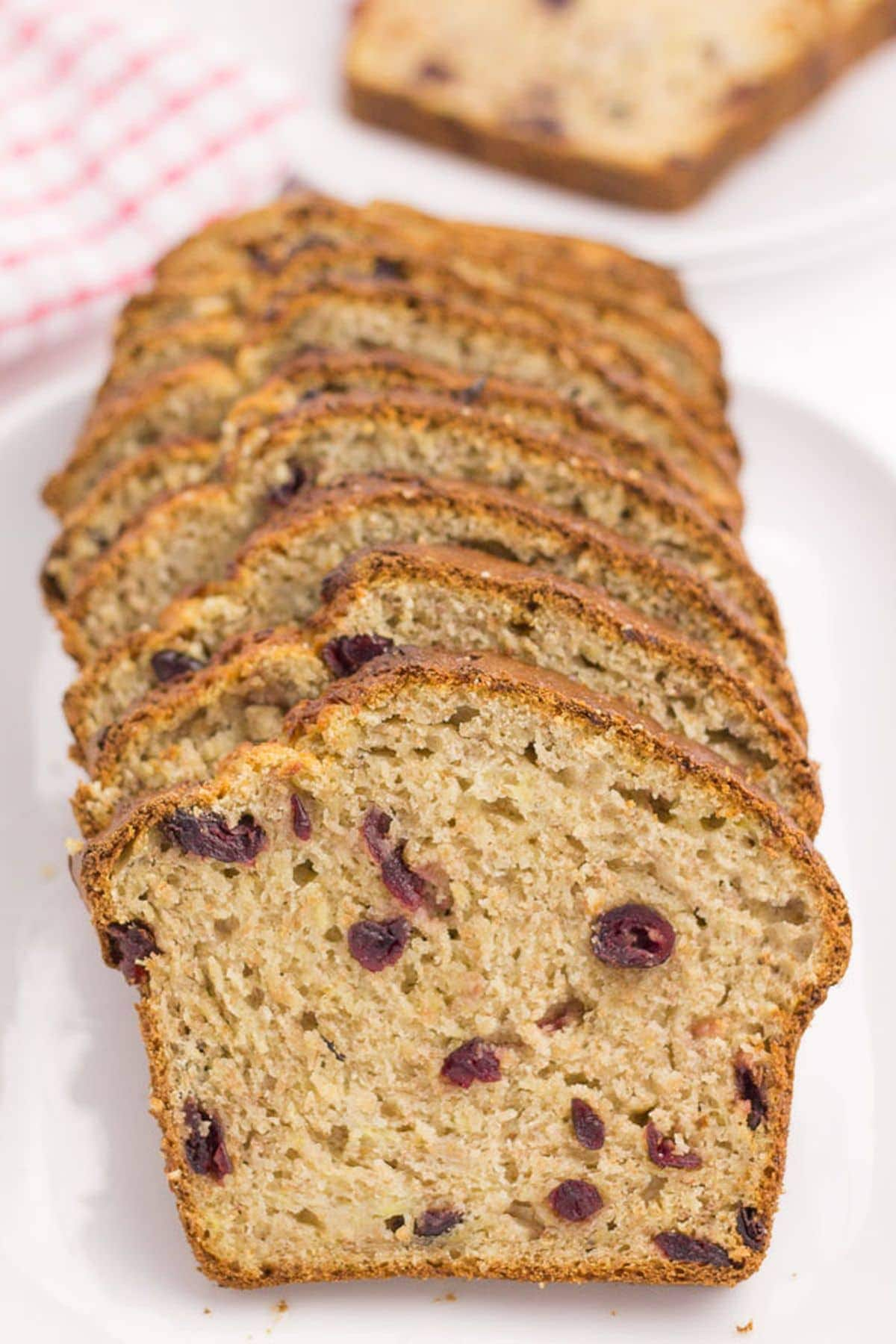 Cranberry banana bread sliced on a serving dish.