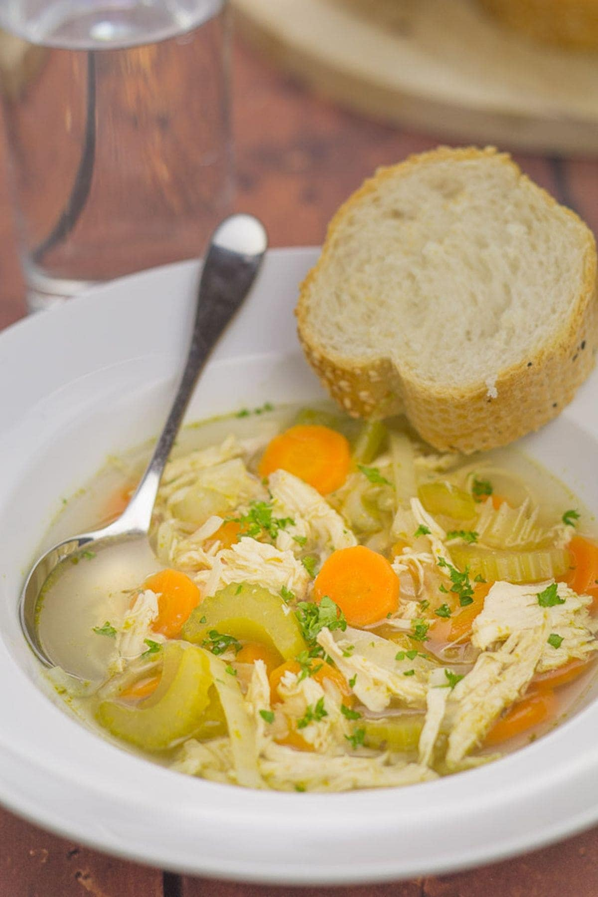 A bowl of simple chicken and vegetable soup with a spoon in. Served with a slice of bread on the side.
