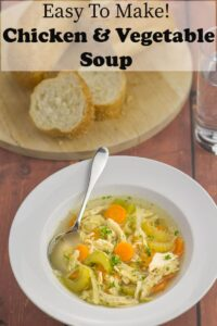 A bowl of simple chicken and vegetable soup in front of a board of sliced bread on it.
