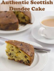 A slice of Scottish Dundee cake on a plate with a cup to tea and the rest of the whole cake in the background. Pin title text overlay at top.