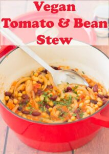 Casserole pot of tomato and bean stew with spoon in it ready to serve.
