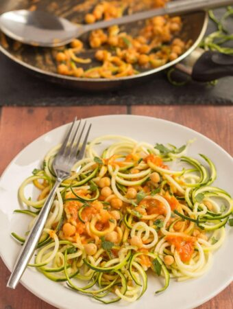 A plate of spiralized courgette spaghetti with chickpeas and the rest of the dish in a pan in the background.