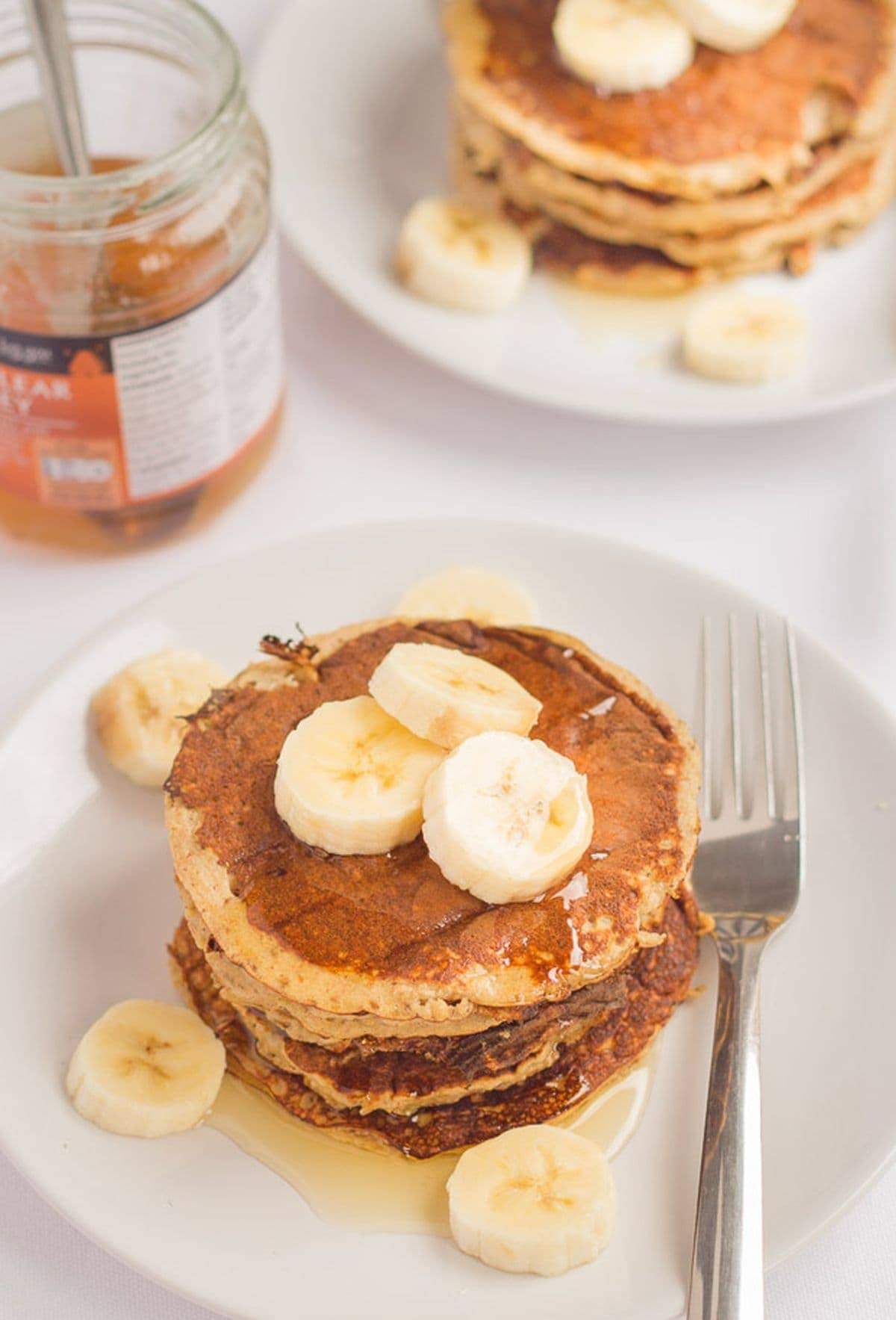 Two plates of banana oat pancakes topped with honey and sliced bananas. A jar of honey with a spoon in between.