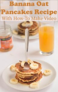 Banana oat pancakes stacked on a plate with a fork in. Orange juice and honey jar in the background.