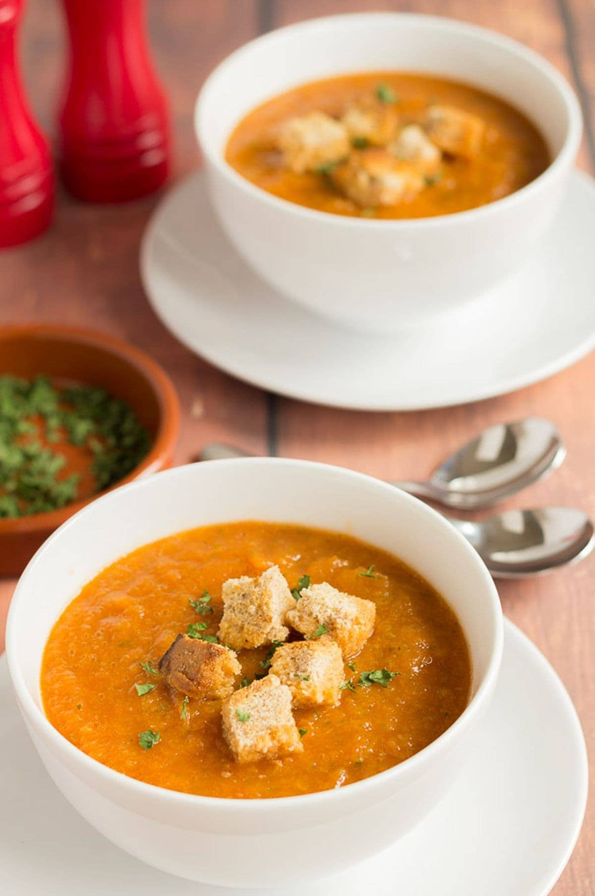 Two bowls of Mediterranean vegetable soup garnished with croutons.