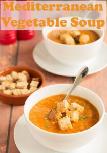 Two bowls of Mediterranean vegetable soup one in front of the other served with croutons. Soup spoons in them and they're ready to eat.