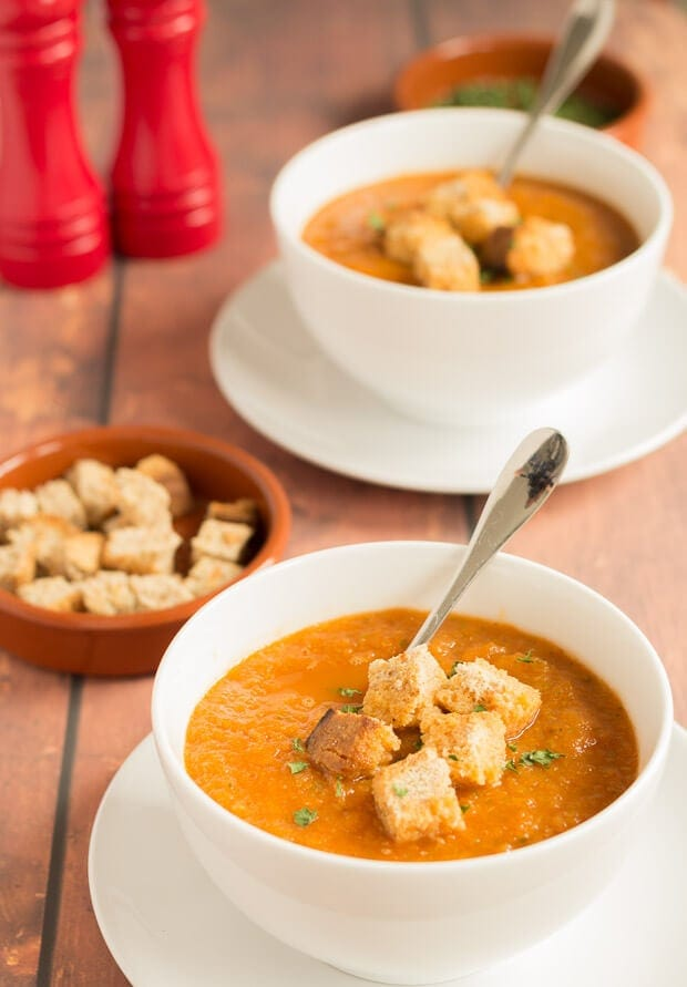 Two bowls of Mediterranean vegetable soup garnished with croutons and spoons in. A dish of croutons to the left side and salt and pepper cellars in the background.