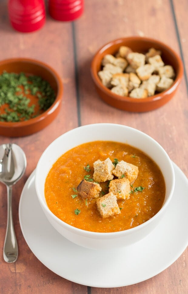 A bowl of Mediterranean vegetable soup garnished with croutons and a spoon to the left side. Dishes of chopped coriander and croutons in the background.