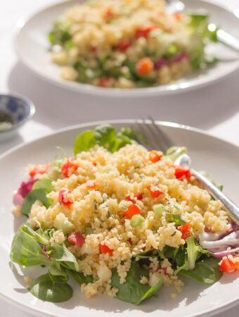Two plates of red pepper and rosemary bulgur wheat salad one in front of the other.