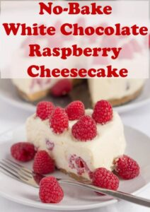 A slice of no-bake white chocolate and raspberry cheesecake on a plate decorated with raspberries and the remainder of the cheesecake in the background.