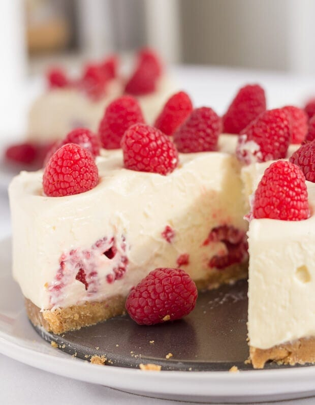Close up front view of no bake white chocolate and raspberry cheesecake with a slice taken out.