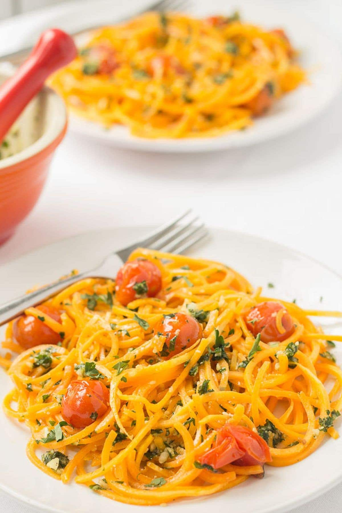 Two plates of butternut squash noodles with spring pesto and roasted tomatoes one in front of the other with forks on. A pestle and mortar in between.